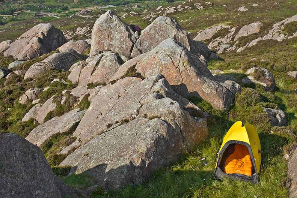 An expedition skills course places a lone yellow tent on moorland