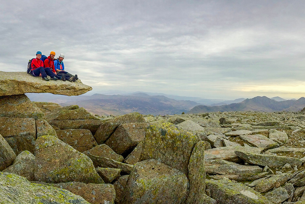 Three people sit on the cantilever stone in Snowdonia after scrambling on a mountaineering skills course
