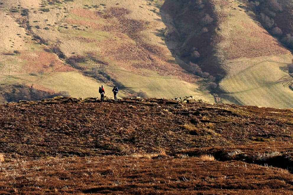 Two people walking on the hills around Edale on a Hill and Moorland Leader course
