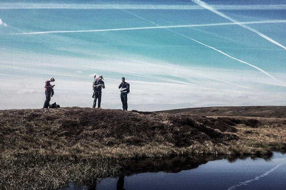 Three people stand by a small moorland pond whilst practicing navigation on a Hill and Moorland Leader Award training course