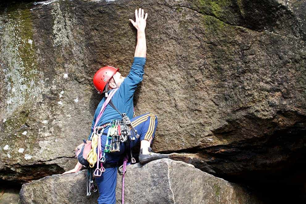A young man stretches for a hold whilst on a Peak District rock climbing instructor course.