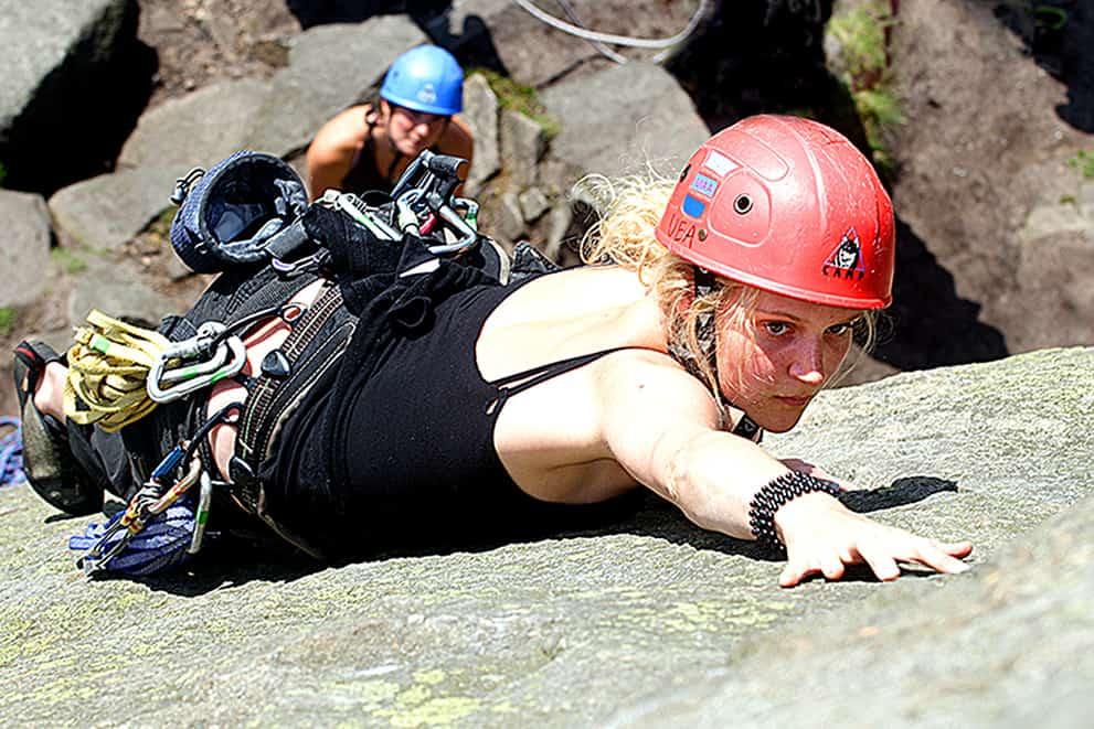 A young lady reaches for a hold whilst rock climbing in the Peak District on a Rock Climbing Instructor (RCI) course