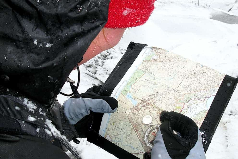 A lady with a map and compass practicing map reading in winter on a hill in the Peak District