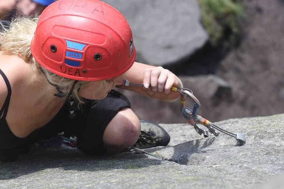 A lady rock climbing and placing gear whilst on a Rock Climbing Instructor (RCI) course in the Peak District national park