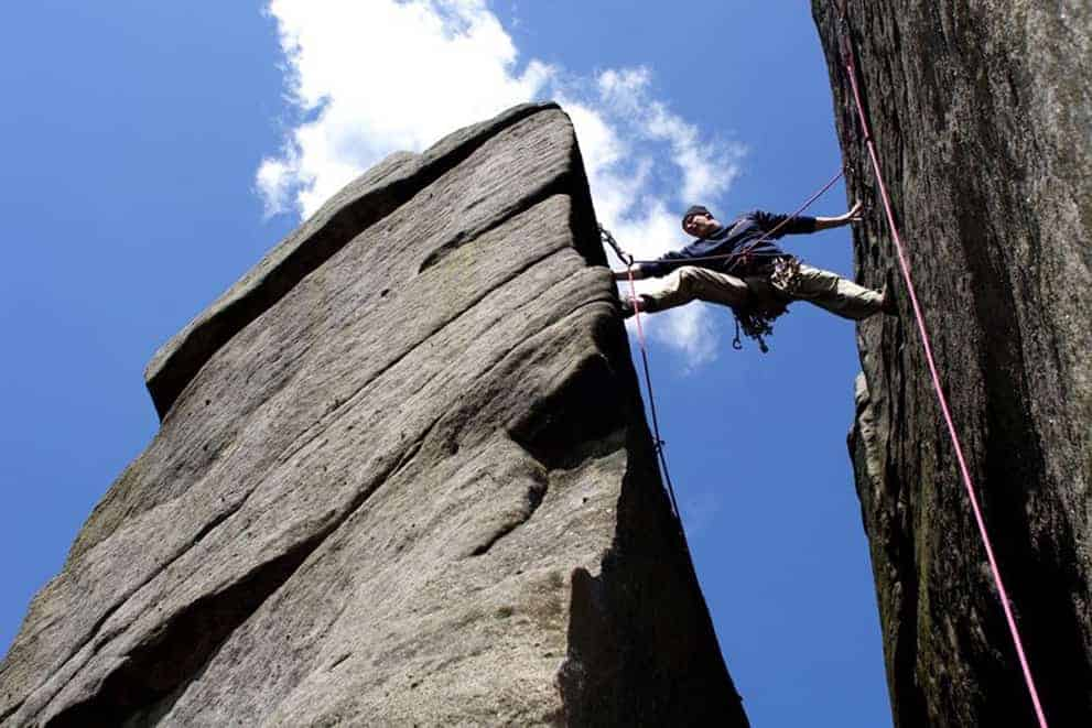 A man rock climbing on Stanage Edge in the Peak District