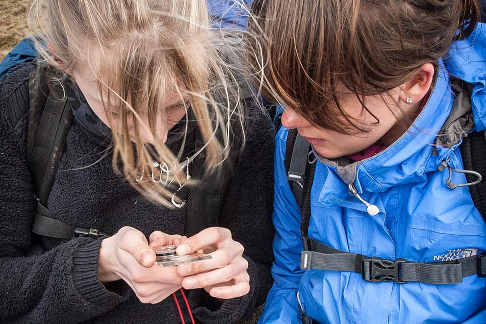 Two young girls study a compass whilst on Peak District navigation courses