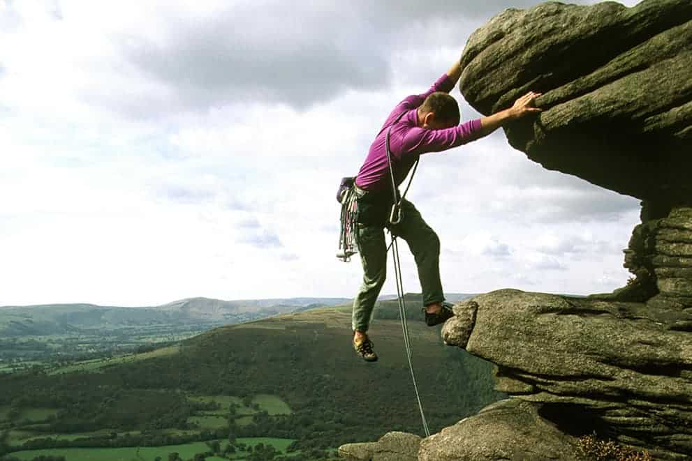 A rock climber on a Mountain Training instructor course nearing the top of a climb in the Peak District
