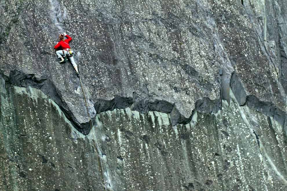 A man on a multi pitch climbing course in the peak District