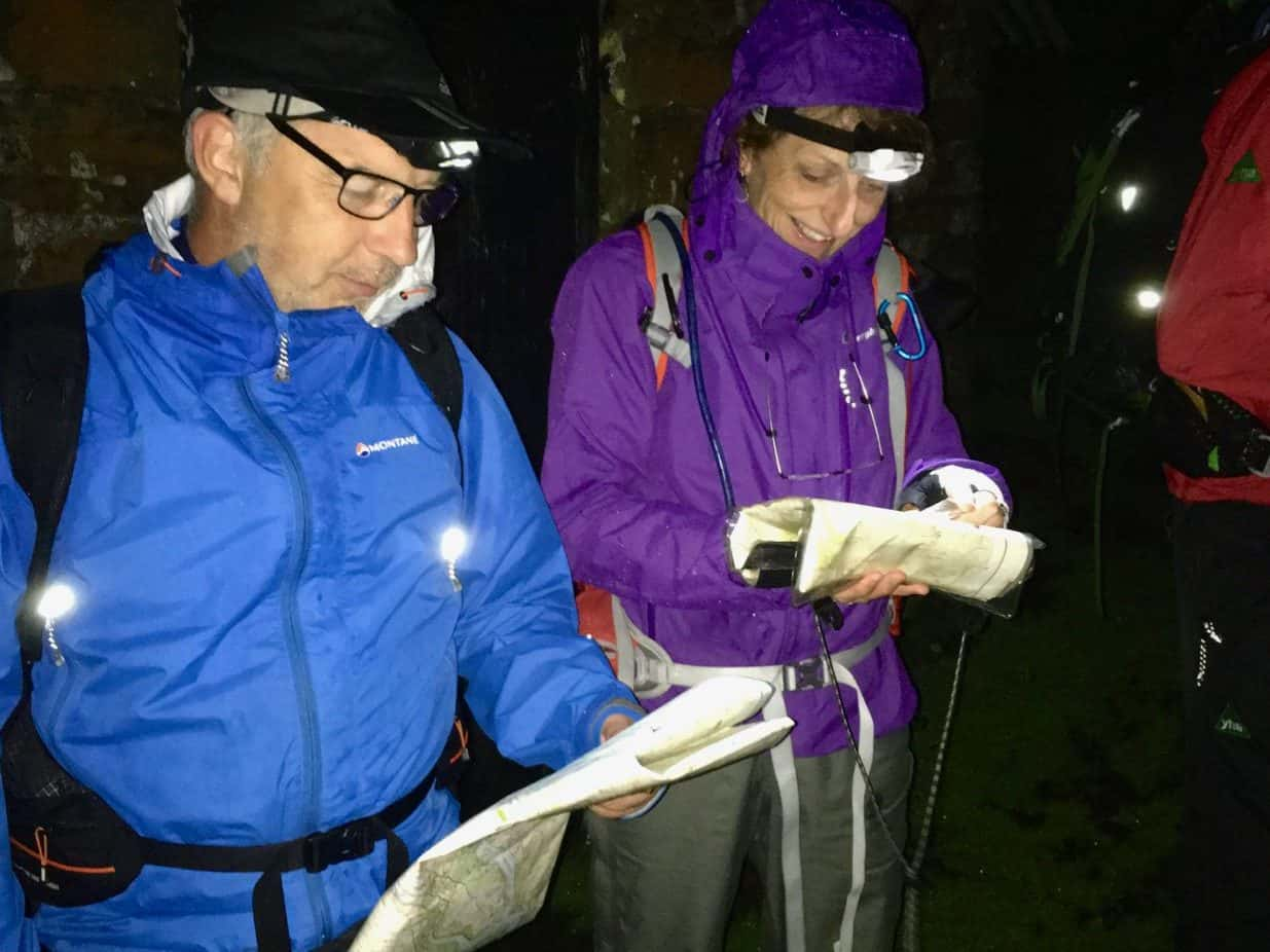 A man and a lady using a map and compass whilst learning to navigate at night on a navigation course in the Peak District.