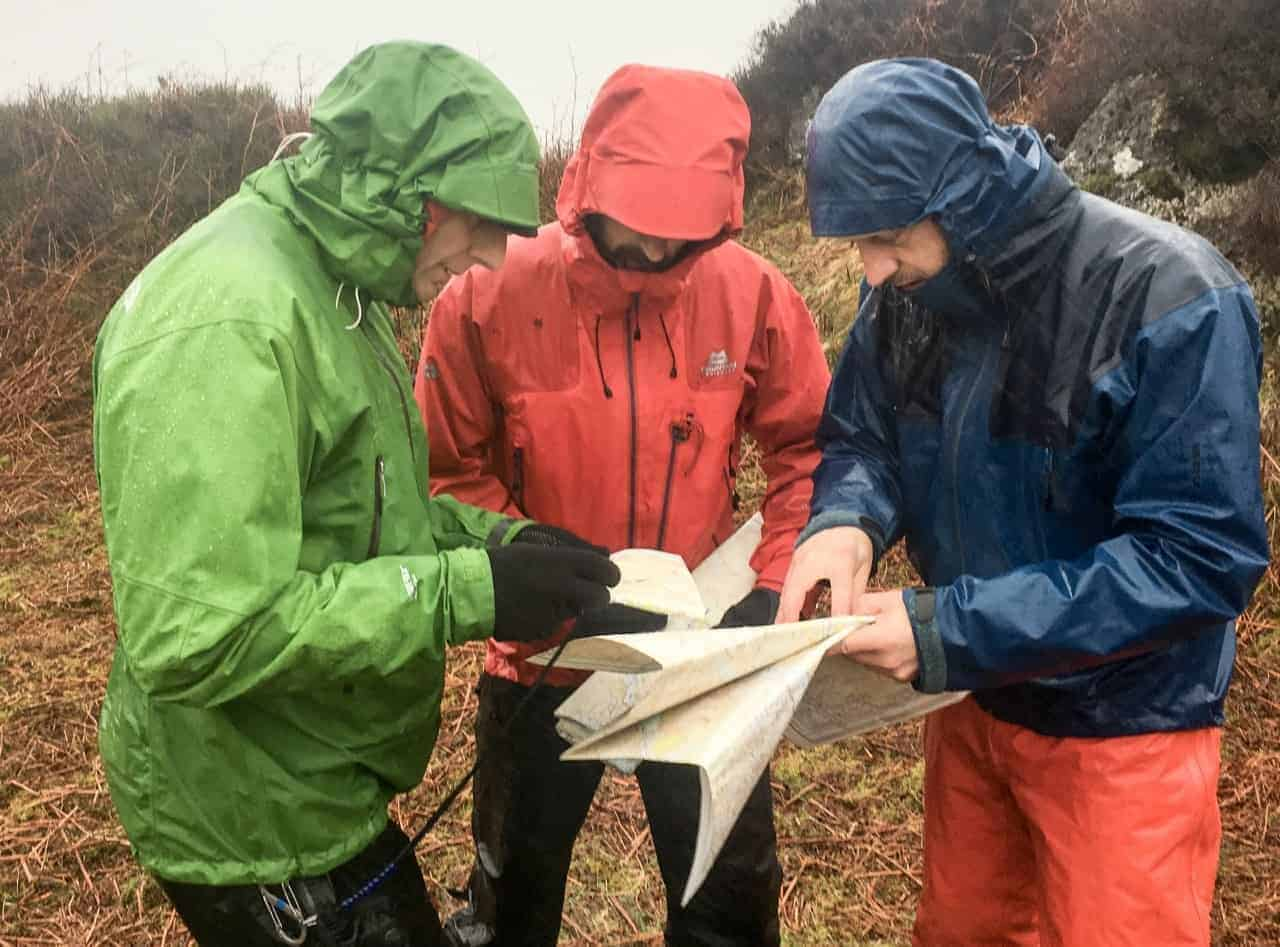 3 men study their maps whilst teaching navigation in the Peak District