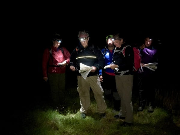 A group practicing night navigation with map and compass