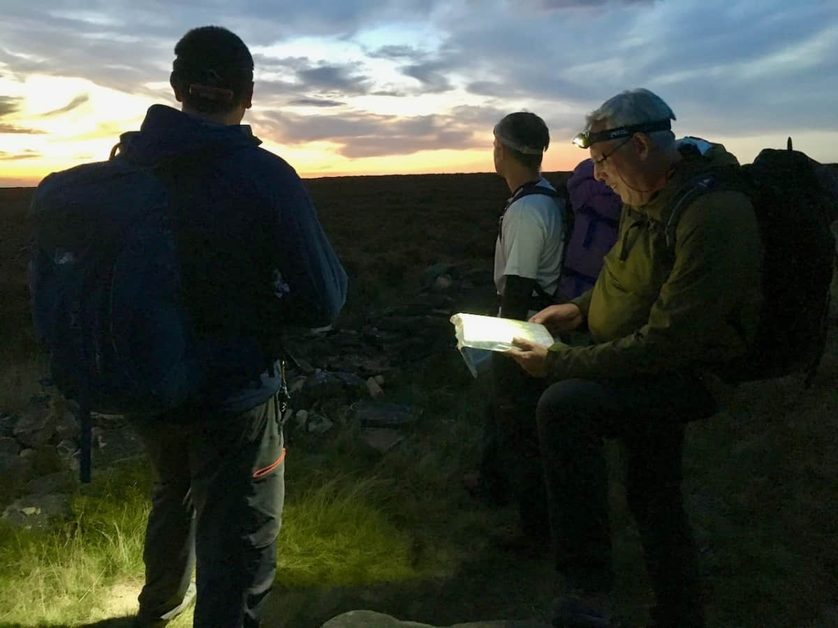 Night navigation course in the Peak District. 3 men with head torches, map and compass.