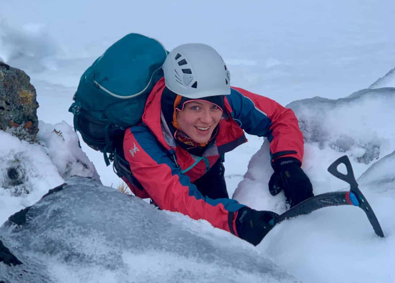 A lady winter walking with ice axe and crampons on a winter skills course in Scotland