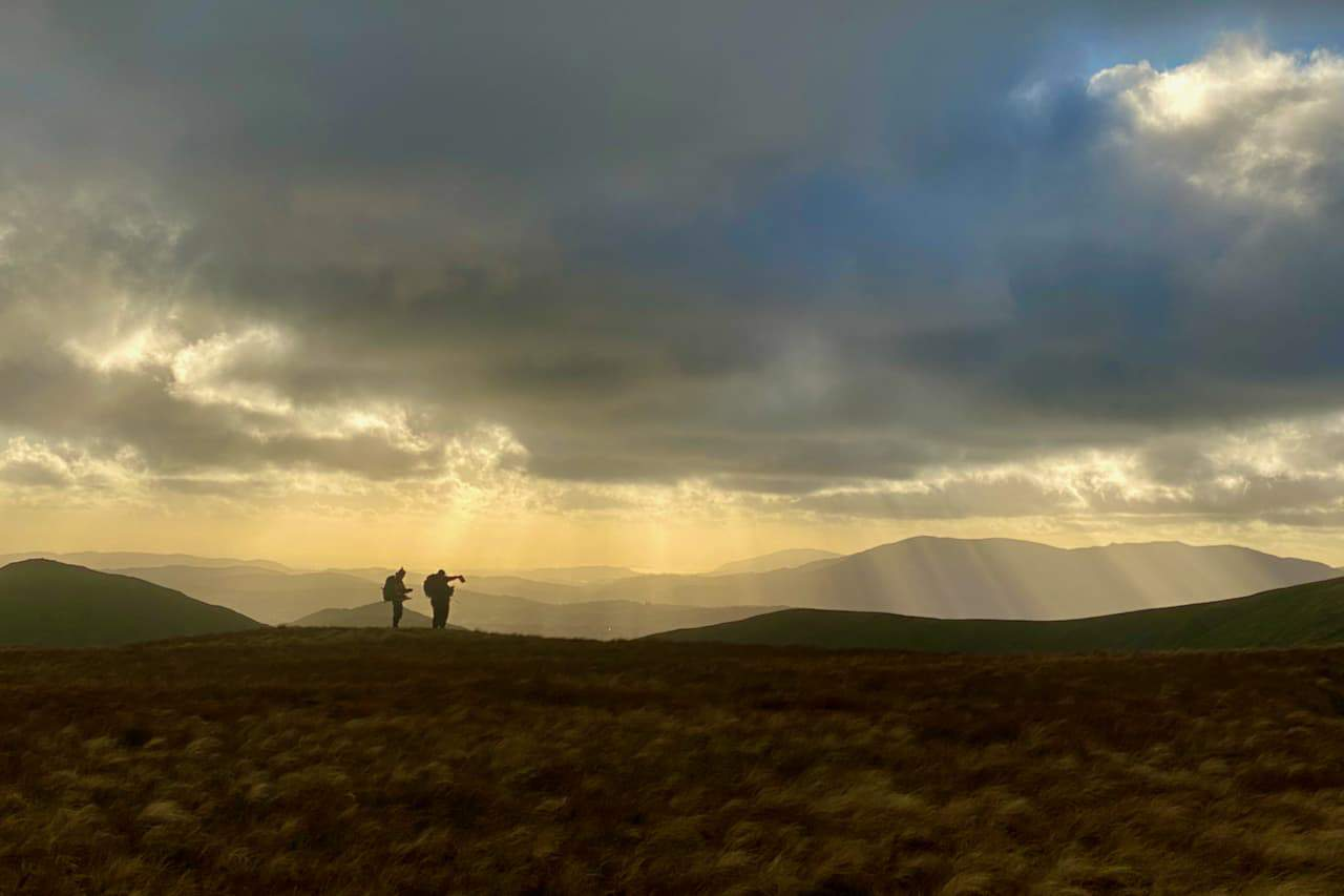 3 people look at a map whilst standing on a summit in Snowdonia on their Mountain Leader course.