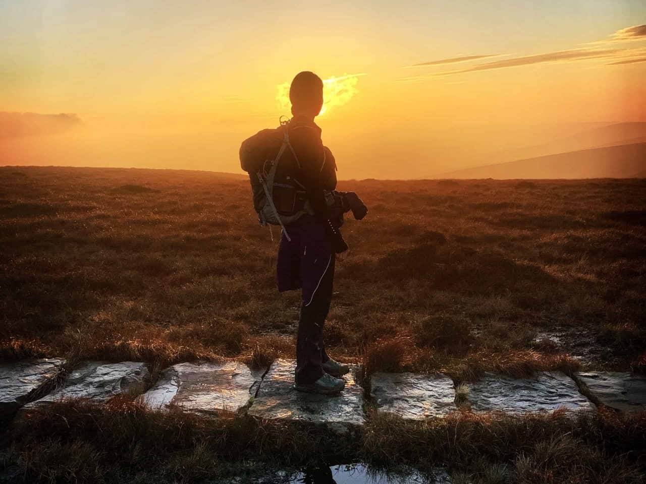 A lady walking in the sunset on the Edale Skyline challenge.