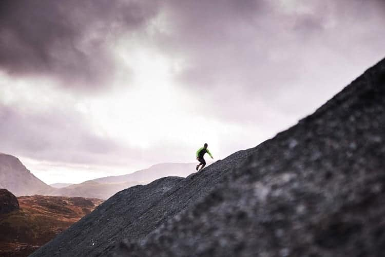 A man runs up a hill on a fell running course in the Peak District