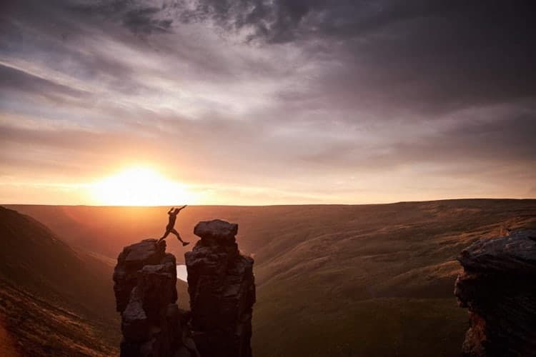 A man strides between two rocks at sunset on a fell running course in the Peak District