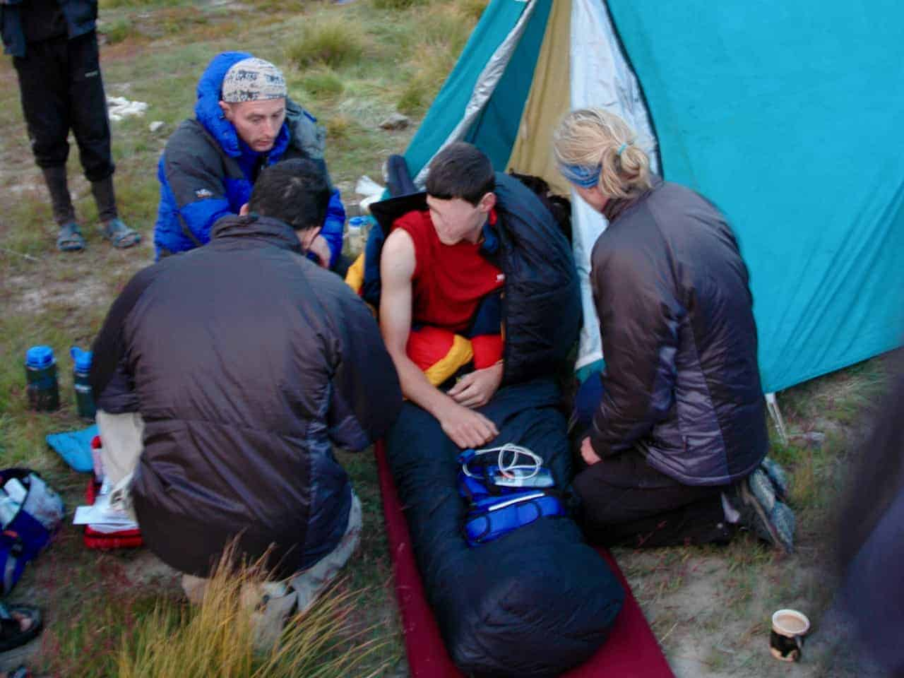 An expedition group gives first aid to a casualty after being on a first aid course in the Peak District