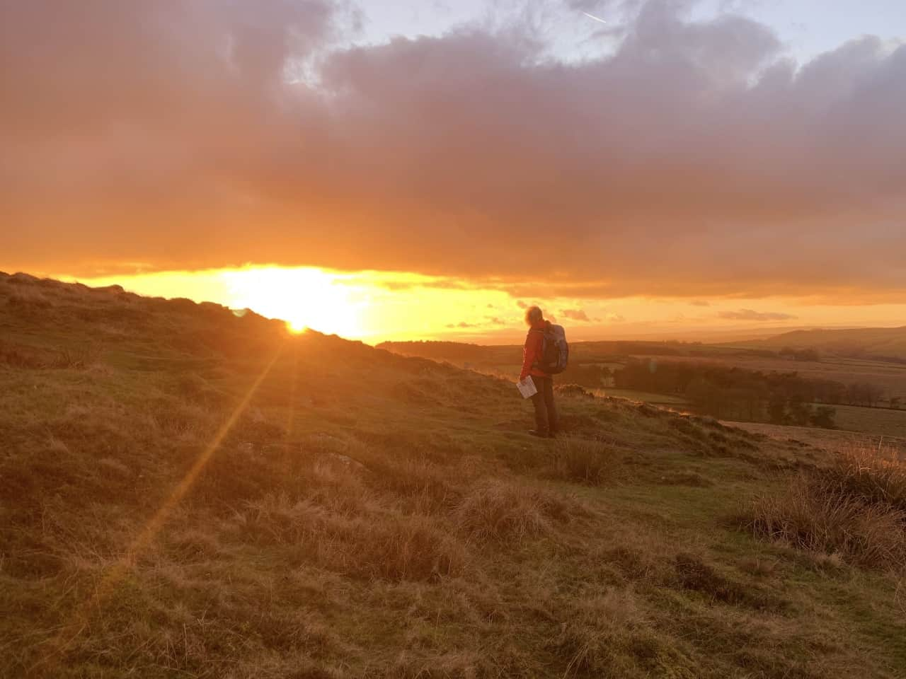 A lady stares into the sunset on a Lowland Leader Course in the Peak District