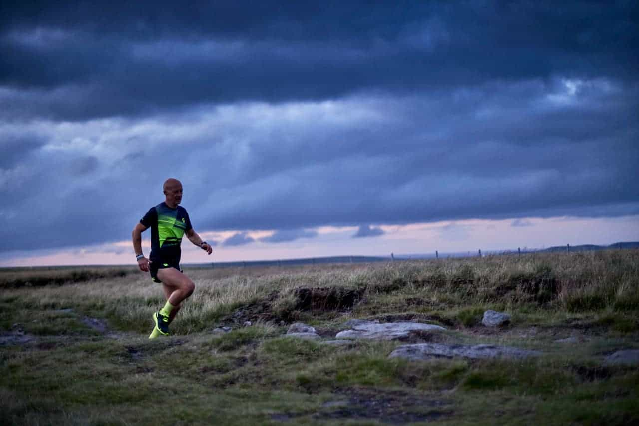 A man runs along a trail on a trail running course in the Peak District